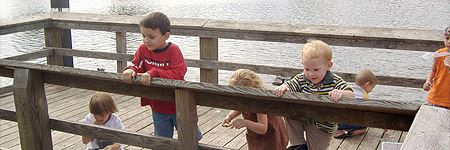 Kids playing and looking over the rail on the fishing dock